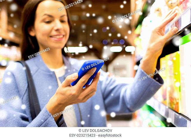 sale, shopping, consumerism and people concept - happy young woman with smartphone choosing and buying food in grocery store or market over snow effect