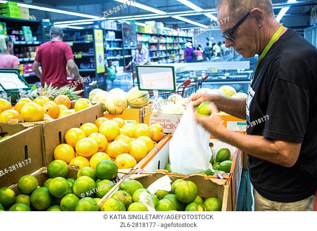 Mature retired senor caucasian man, in his 60's, 70's, doing his grocery shopping on vacation, looking at vegetables and fruits