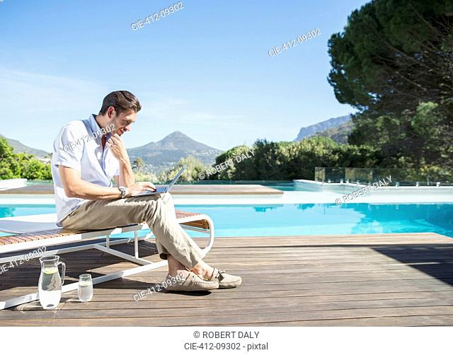 Man using laptop at poolside