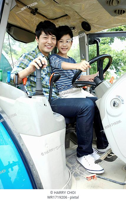 A father and a son driving a tractor
