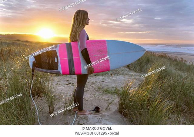 Young surfer woman on the beach