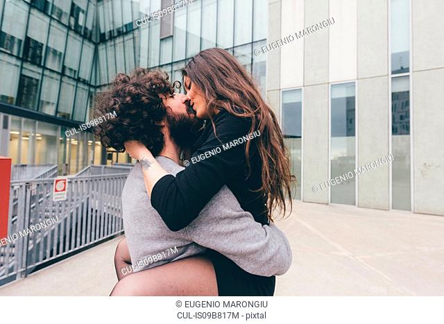 Young couple outdoors, kissing, woman's legs wrapped around man