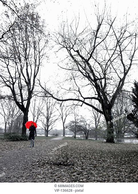 junge Frau mit rotem Schirm an der Alster in Hamburg. - Hamburg, GERMANY, 01/01/2006