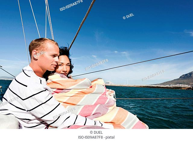 Young couple on yacht, woman wrapped in blanket