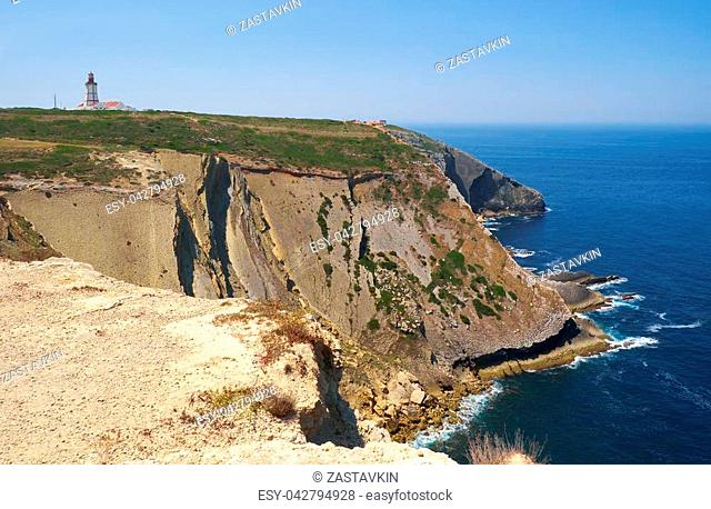 The view of a big limestone cliffs over Praia do Cavalo or Horses beach and a lighthouse on the cape Espichel. Sesimbra. Portugal