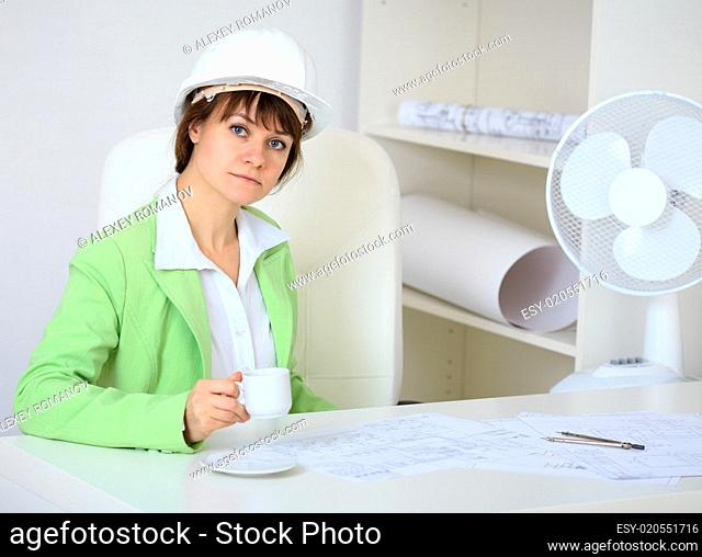 Woman - a builder in helmet with cup in hand