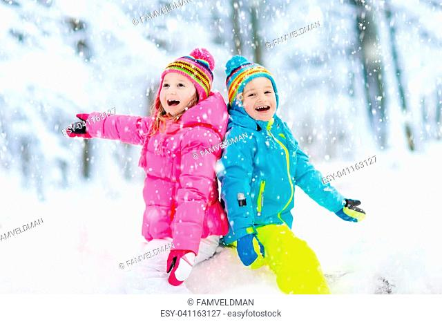 Kids playing in snow. Children play outdoors on snowy winter day. Boy and girl catching snowflakes in snowfall storm. Brother and sister throwing snow balls
