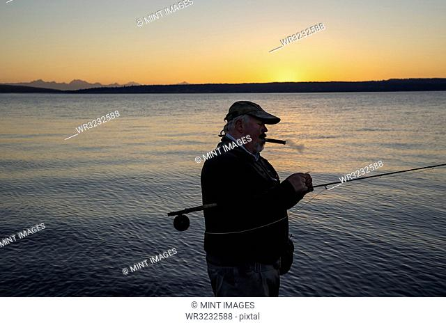 A Caucasian senior fly fisherman enjoys a sunrise cigar before fly fishing for searun coastal cutthroat trout and salmon on the west coast of the USA