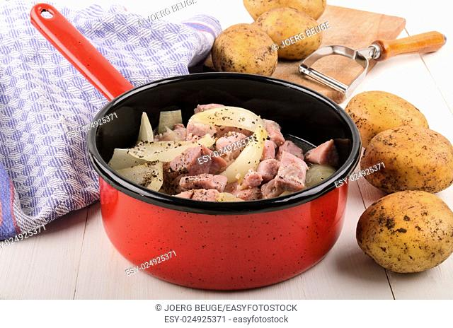 cooked onions and bacon cubes with coarse pepper in a pot, next to raw potatoes and vegetable peelers