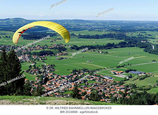 Paraglider gliding from Buchenberg Mountain above Buching, East Allgaeu, Swabia, Bavaria, Germany, Europe