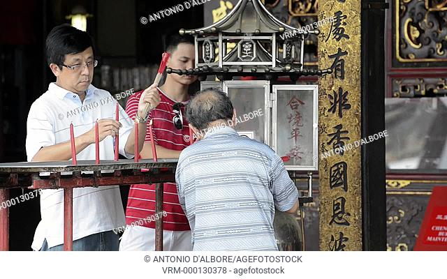 Chinese followers lighting up candle in the Cheng Hoon Teng Temple. Malacca. Malaysia