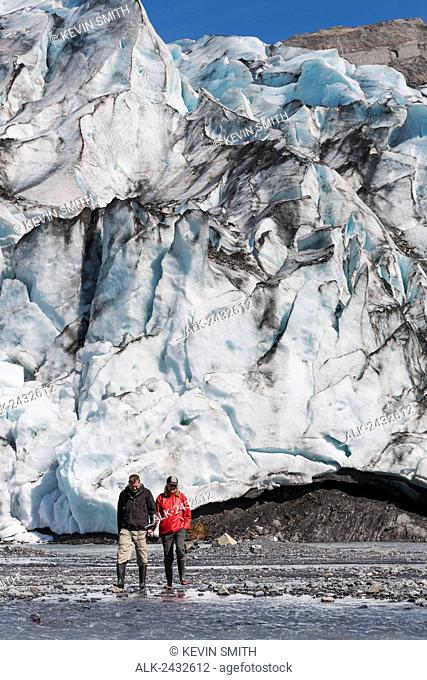 Couple hold hands while exploring Shoup Glacier, Shoup Bay State Marine Park, Prince William Sound, Valdez, Southcentral Alaska