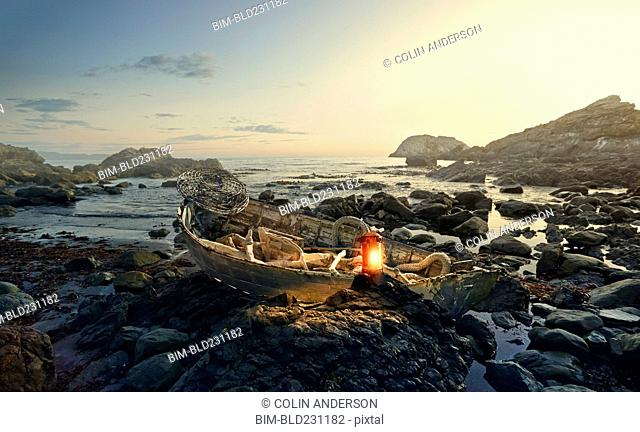 Lantern glowing on rowboat at rocky shore