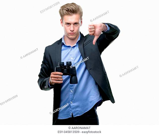Young handsome blond man looking through binoculars with angry face, negative sign showing dislike with thumbs down, rejection concept