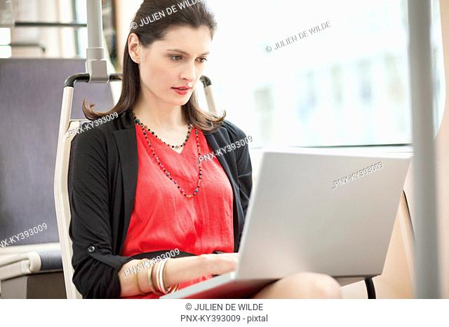 Woman traveling in a bus and using a laptop