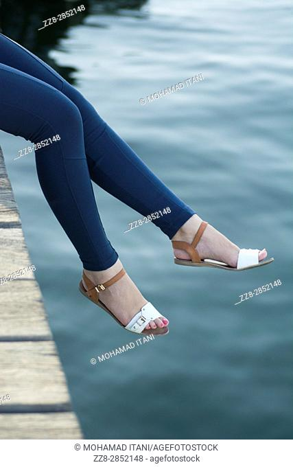 Close up of a woman's legs sat on the wharf by the sea
