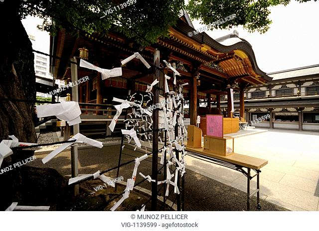 JAPAN, TOKYO, 11.07.2008, Omikuji (foreground). Fortune papers rolled and tied to the wire when the fortune found is not much good