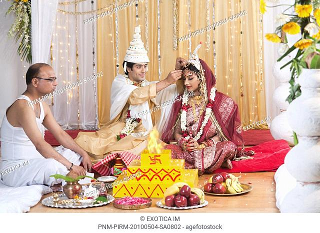 Couple performing Sindoor Daan ceremony in Bengali wedding