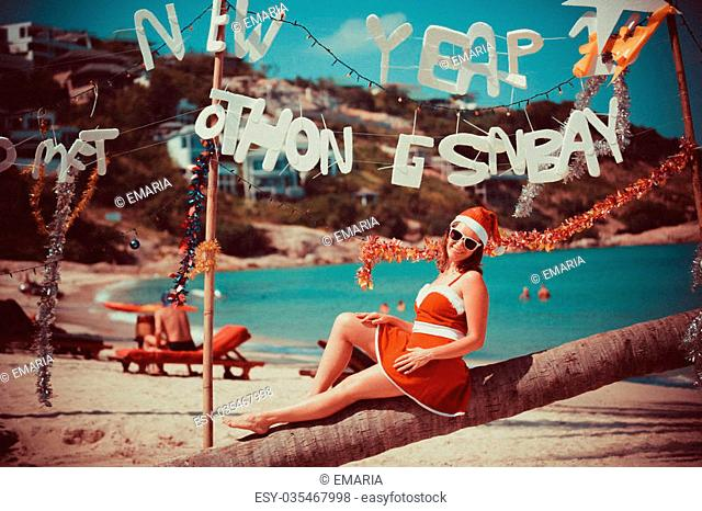 Cute woman in red dress, sunglasses and santa hat sitting on palm tree at exotic tropical beach. Holiday concept for New Years Vintage Cards in retro colors