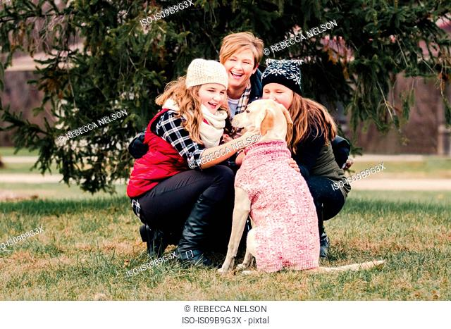Sisters and their mother crouching to pet dog in garden