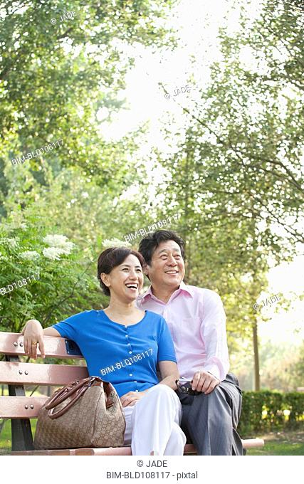 Chinese couple relaxing on park bench