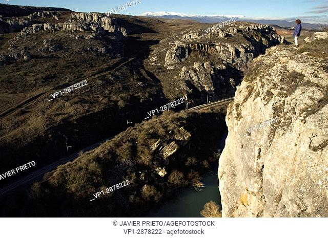 A woman contemplates the abyss from the top of the cuts cut by the Pisuerga River as it crosses the La Horadada Canyon within the Las Loras world geopark