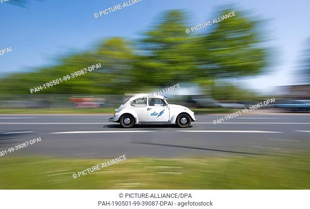 """01 May 2019, Lower Saxony, Hanover: A VW Beetle drives to the 36th """"""""Maikäfertreffen"""""""" on a fair parking lot. More than 3000 owners of beetles and other VW..."""