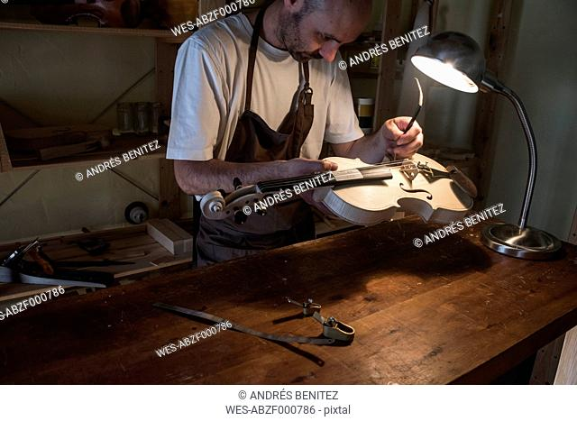 Luthier adjusting the sound post of a violin in his workshop