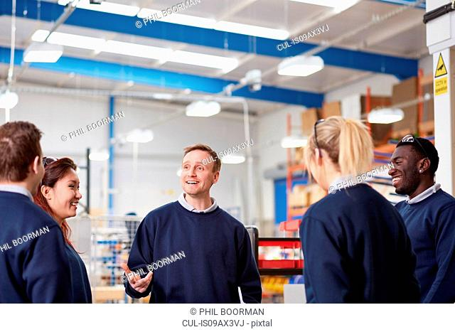 Manager explaining to team in manufacturing factory