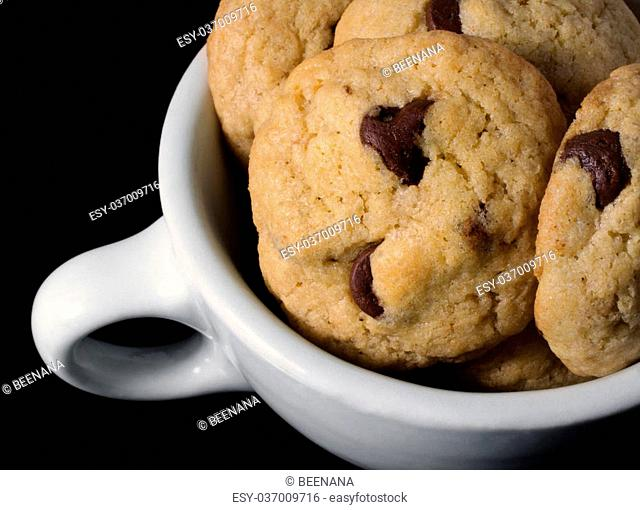 A close-up photograph of soft, homemade chocolate chip cookies in a white coffee cup on a black background
