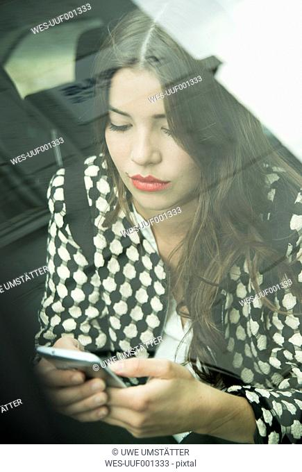 Portrait of young woman sitting in car using her smartphone