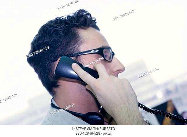Side profile of a businessman talking on a telephone
