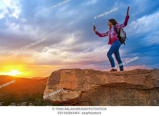Hiker teen girl selfie smartphone on peak of mountain at sunset
