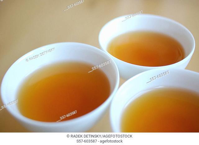 Black Asian tea in white bowls