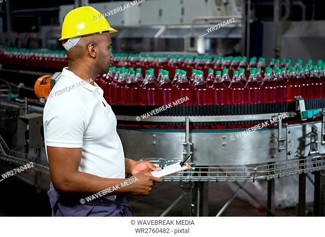 Male worker inspecting bottles in juice factory