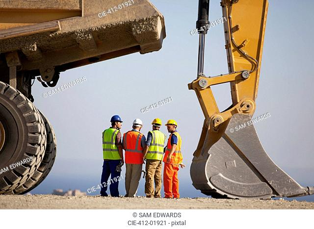 Workers talking by machinery in quarry