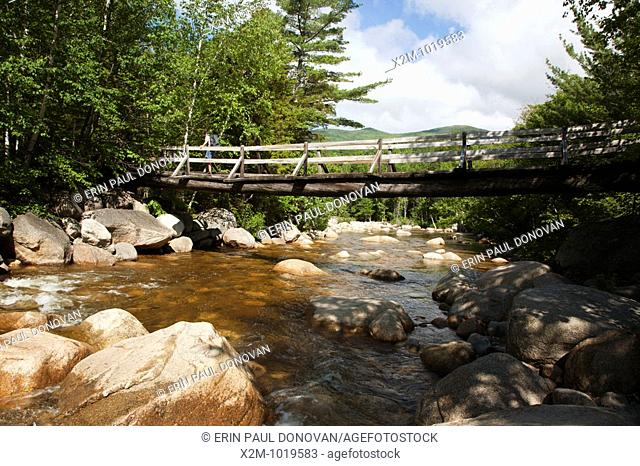 Pemigewasset Wilderness - A hiker on foot bridge which crosses over the Pemigewasset River on Thoreau Falls Trail  Located in Lincoln, New Hampshire USA
