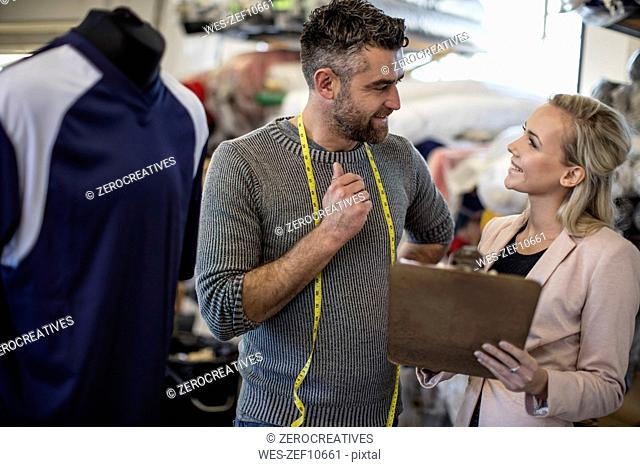Tailor talking to woman with clipboard in workshop