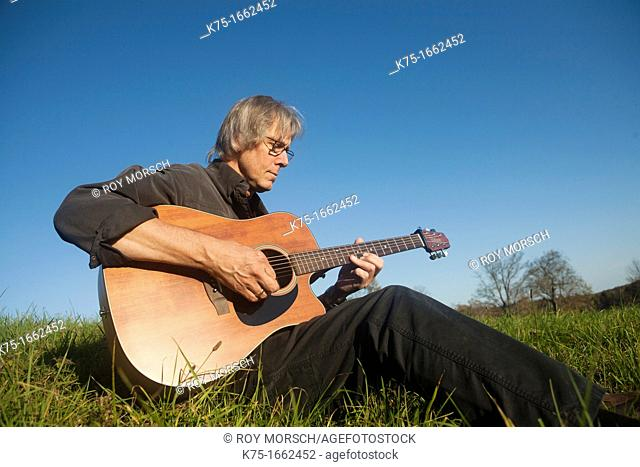 Guitarist playing music in field