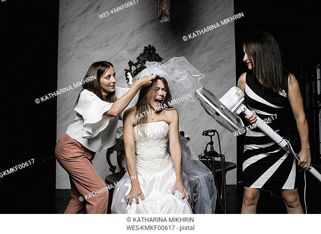 Playful friends and bride during wedding preparation