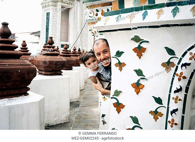 Thailand, Bangkok, Wat Arun, Portrait of happy father and daughter visiting the Buddhist temple
