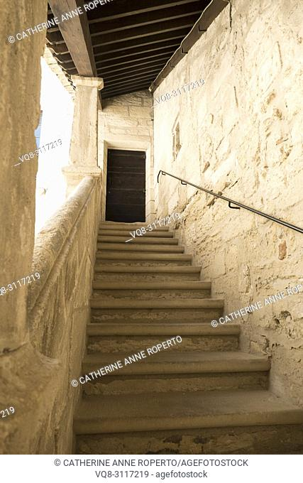 Stone steps ascending, with wooden roof beams appearing to descend in a repeating geometric pattern to meet an old wooden door set in the sunlit chalky walls of...