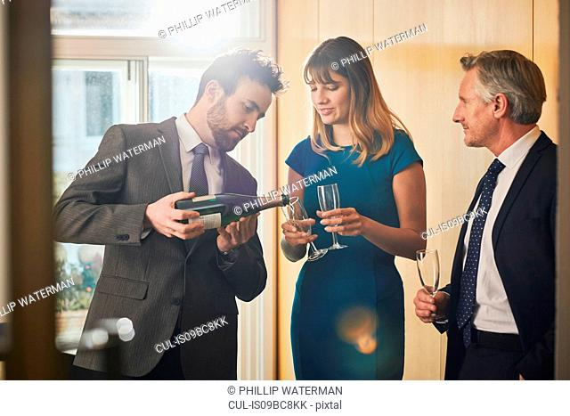 Businessman pouring champagne at office celebration