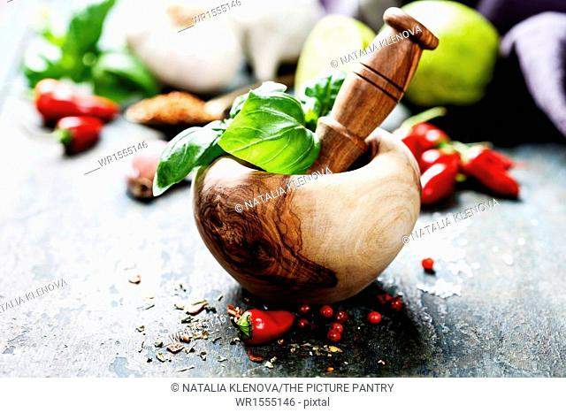 Red Hot Chili Peppers, herbs and spices with Mortar and Pestle over wooden background