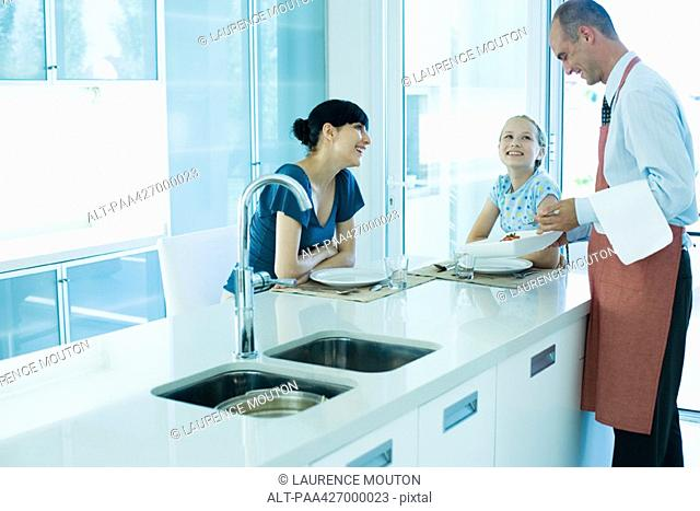 Man serving woman and girl in kitchen
