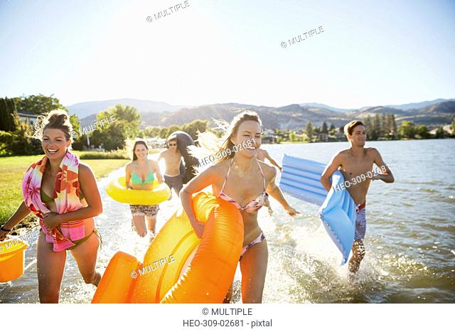 Young friends with inner tubes and inflatable rafts running in sunny summer lake