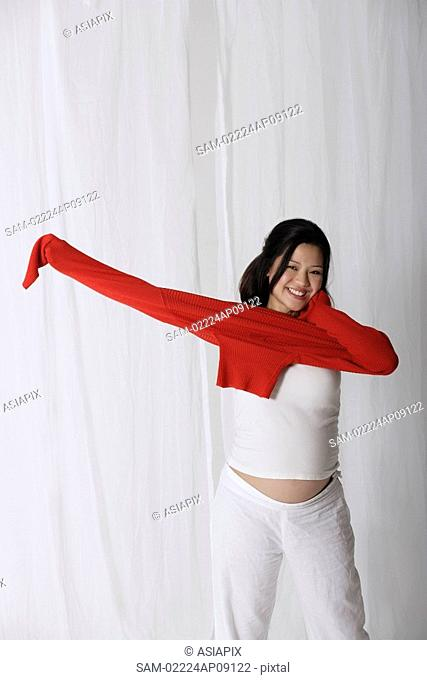 Pregnant woman putting on red sweater