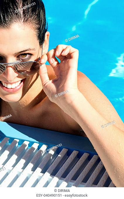 Beautiful and sexy woman face looking over her sunglasses in a pool in summer holidays. Brunette girl relaxing on hot sunny day