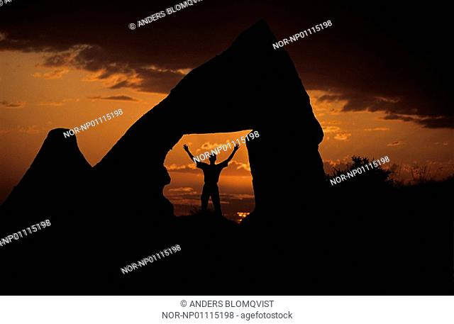 Silhouette of a person raising arms whilst standing in mid of rocks at dusk