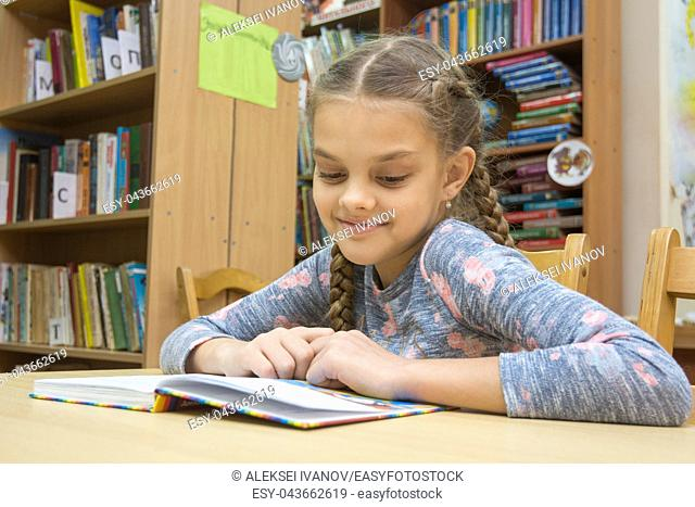 A girl with a smile reads a book in the reading room